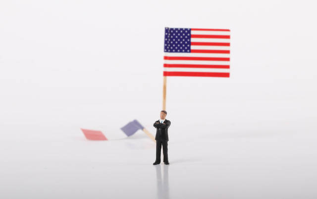 Businessman standing in front of flag of USA and fallen flag of France