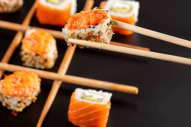 Close-up, spicy roll with tobiko caviar in chopsticks