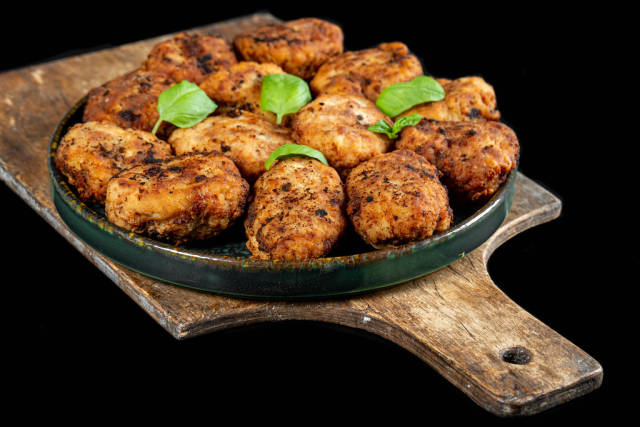 Fresh homemade fried cutlets with basil leaves on dark background