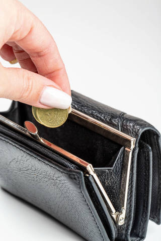 Close-up, female hand puts coins in a wallet