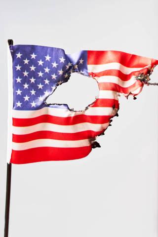 Burned US national flag against bright background