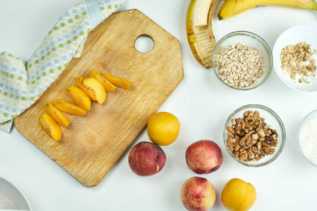 Preparing nutritious snack with oats, peach and banana fruits