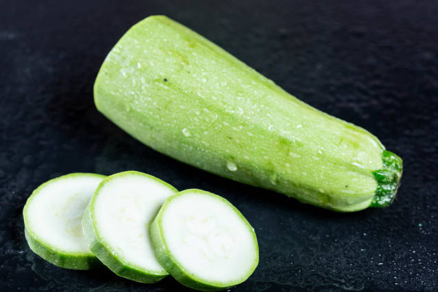 Zucchini with slices on a black background.