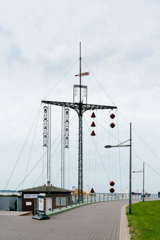 Decorative mast with bells next to the beach and Maritime Museum