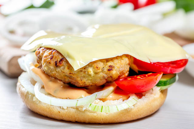 Half a hamburger bun with a filling close-up