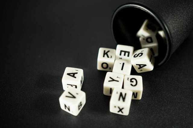Letter dice coming out of a small black cup