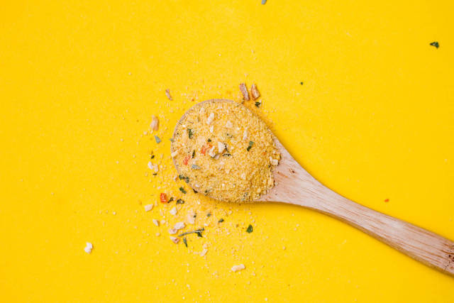 Top view of wooden spoon with yellow spice on yellow background