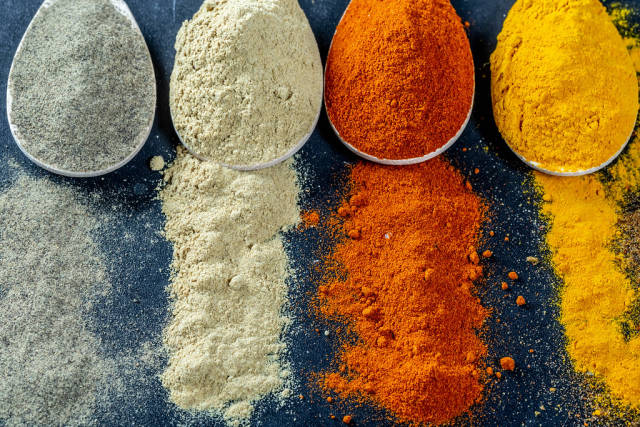 Powder multi-colored spices scattered and in wooden spoons