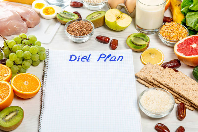 """Notebook with the inscription """"diet plan"""" and ingredients around"""