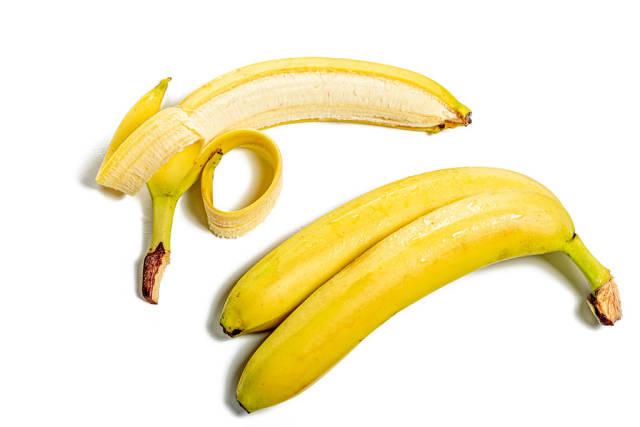 Ripe whole bananas and peeled on white background