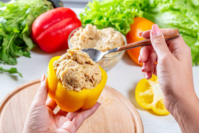 The woman stuffed bell pepper with minced meat