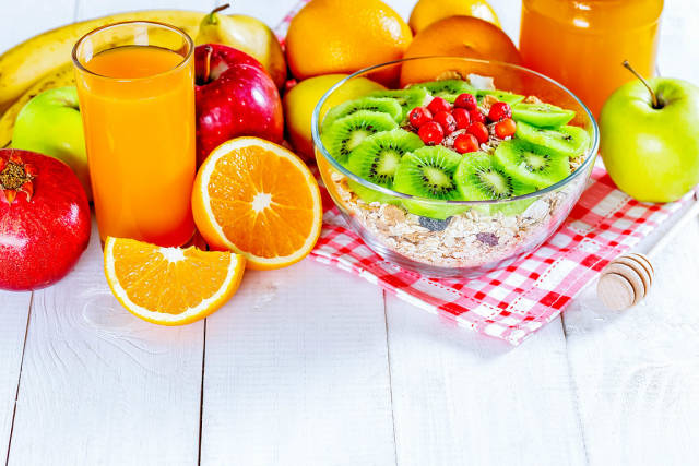 A variety of cereals with honey, fresh fruit and juice for a healthy diet
