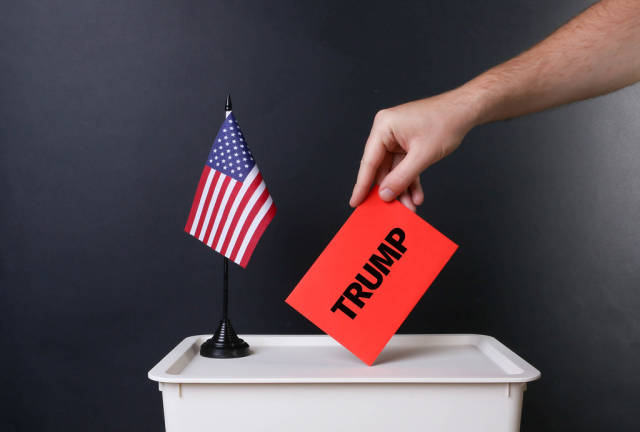 Voter holds red envelope with Trump text