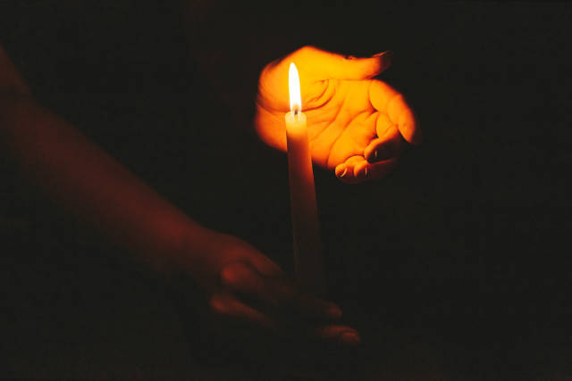 Religious concept, hands holding a burning candle on dark background