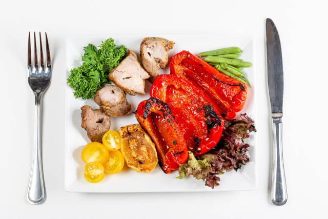 Top view, grilled meat with vegetables on a white background with a knife and fork