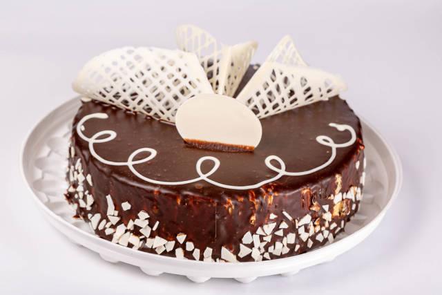 Whole brown chocolate cake with white chocolate decor