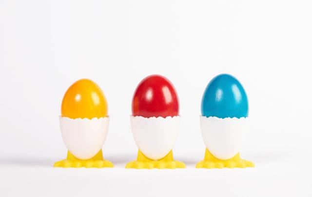 Boiled eggs in holders on white background