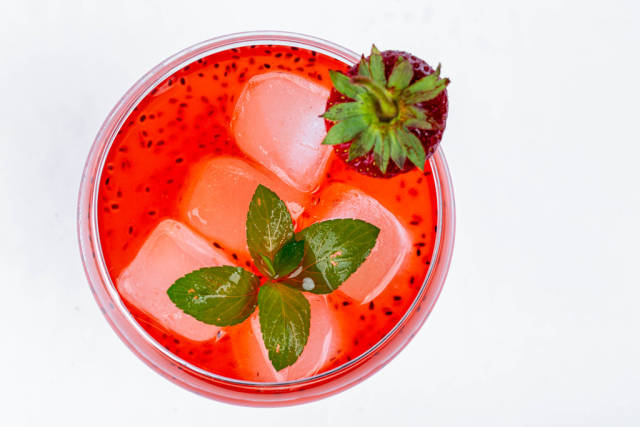 Fresh summer cocktail with strawberry and ice cubes. Top view