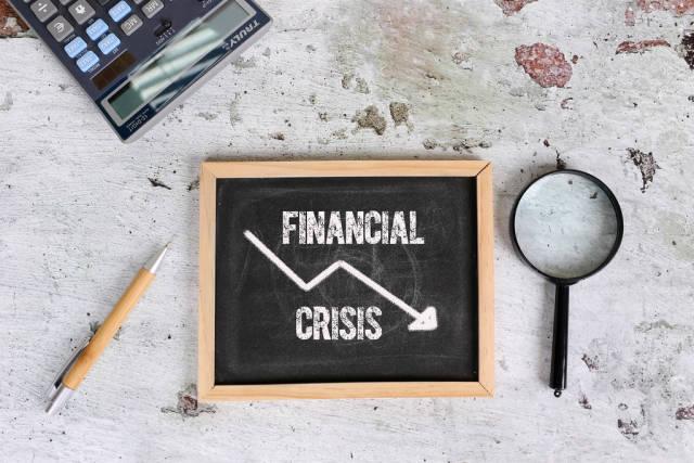 Text Financial Crisis written on a mini blackboard. Economic crisis concept
