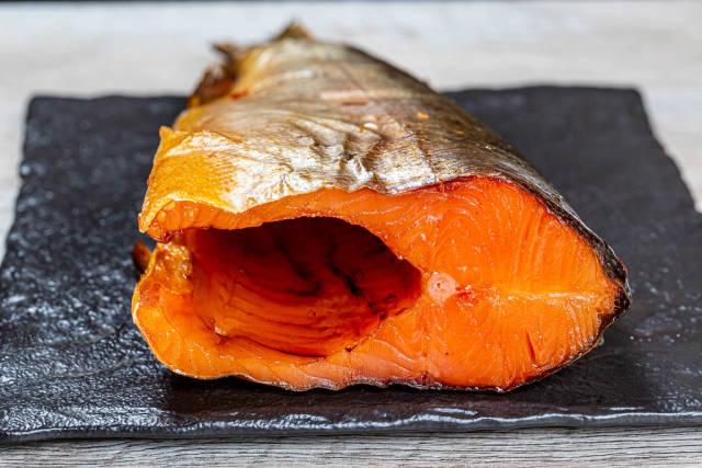 Close up of smoked salmon on a black stone tray