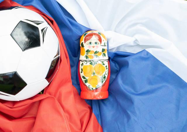 Matrjoschkapuppe und Fußball auf russischer Fahne