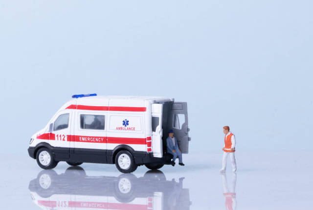Ambulance, medical worker and patient on light blue background