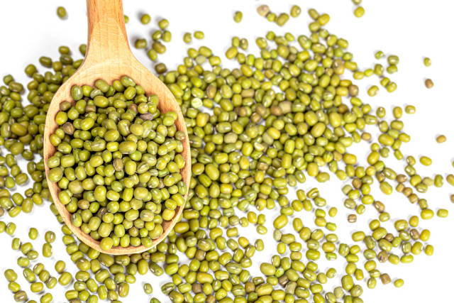 Mung beans in wooden spoon on white background