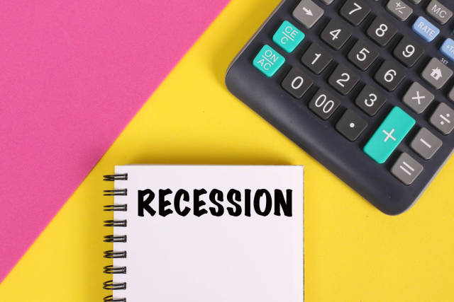 Recession text in notebook with calculator on colorful background