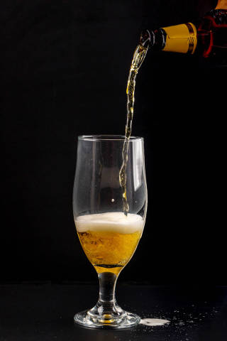 Light beer is poured into a glass on a black background