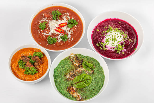 Four bowls with delicious vegetable soups on a white background