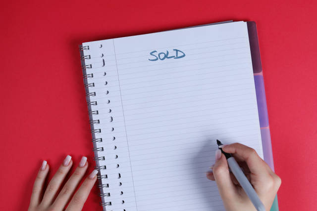 Woman writing Sold text on notebook, red background
