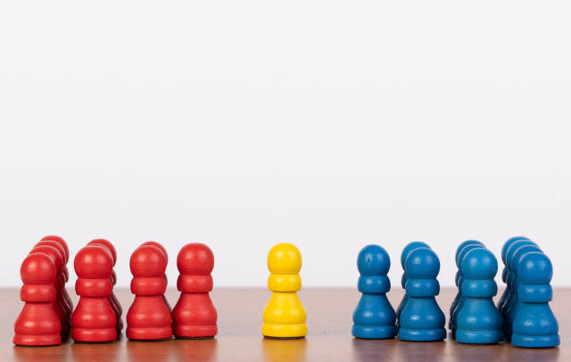 Single yellow pawn figure between red and blue groups