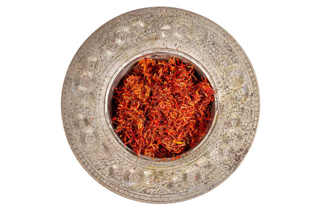Top view, saffron spice in metal bowl on white background