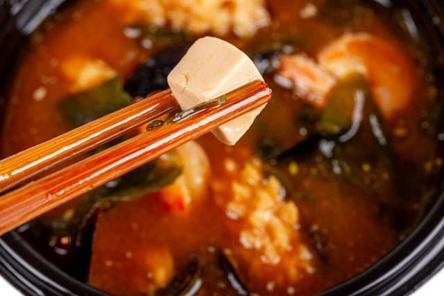 In wooden chopsticks a cube of tofu cheese on the background of miso soup