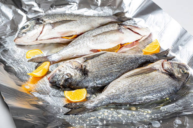 Four raw fish with spices and lemon slices on foil