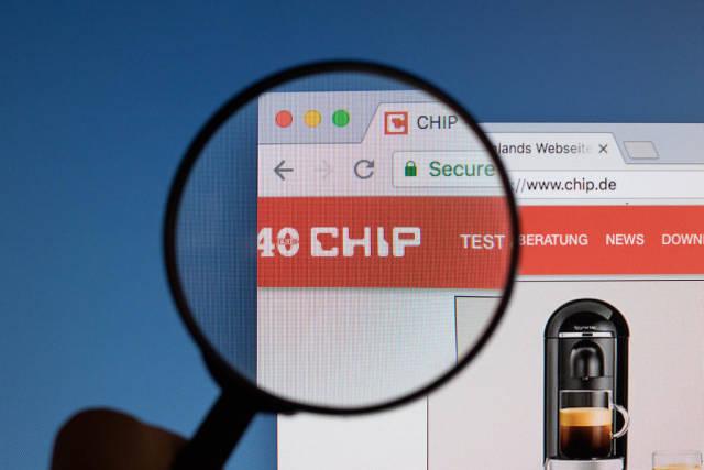Chip.de Logo am PC-Monitor, durch eine Lupe fotografiert