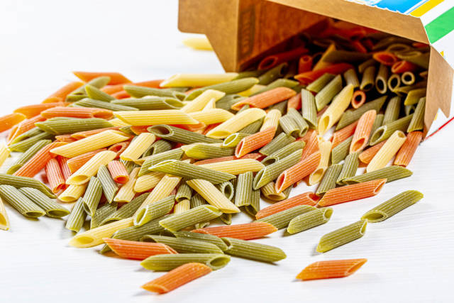 Orange, green and yellow raw pasta spilled from the box