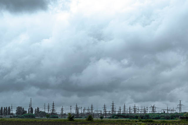 High-voltage power lines with sky background. Electricity distribution station