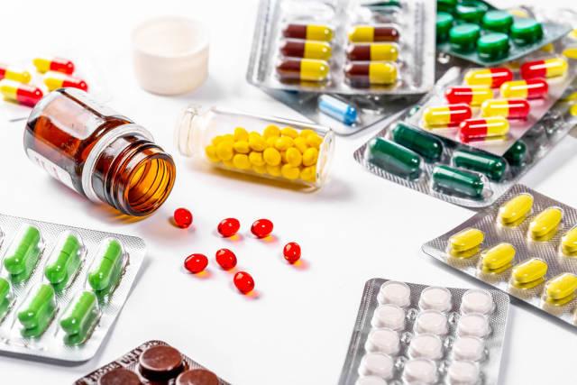 Viele verschiedene Tabletten und Pillen in allen Farben und Formen, auf weißem Untergrund
