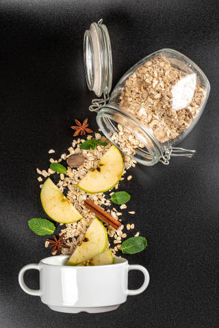 Scattered oatmeal from a jar with pieces of apple, spices and mint on a black background with a bowl, top view