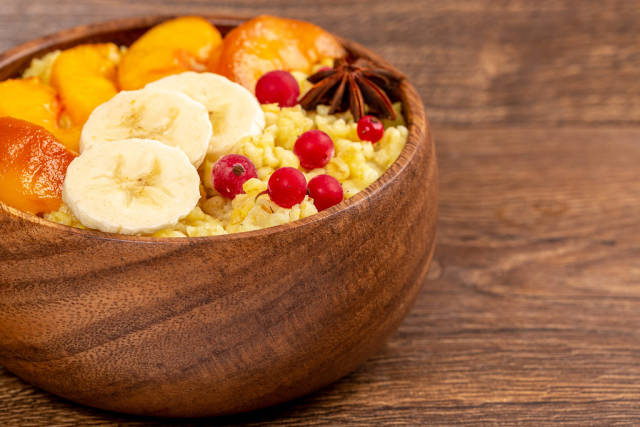 Close-up, bulgur porridge with slices of peach, banana and currant on a wooden background