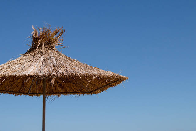 Umbrella made of straw at blue sky background