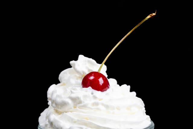 Cherry with whipped cream on a black background