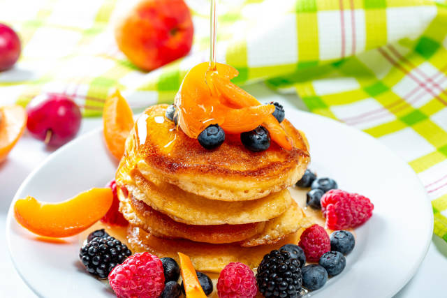 Plate with tasty pancakes and berries, honey pours from the top