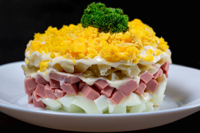Close up layered salad with vegetables and ham on black background
