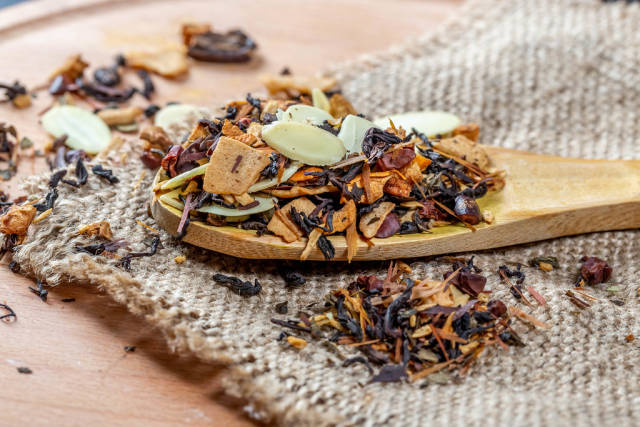 Delicious tea with dried fruits and nuts in a wooden spoon