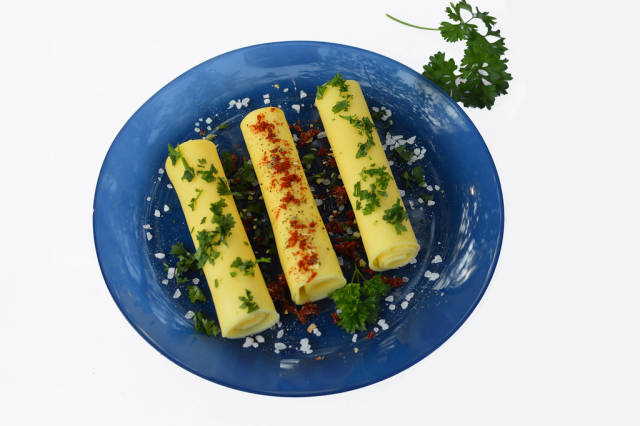 Rolls of cheese with herbs and peppers