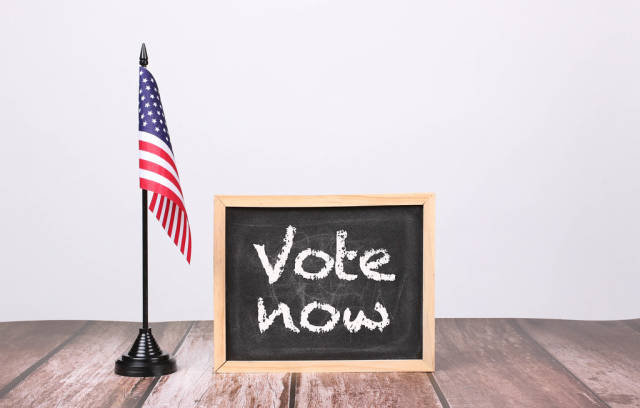 American flag with small blackboard and Vote now text