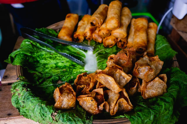 Deep fried delicacies on spinach on display