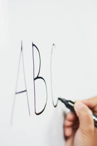 English for kids. First lesson. A teacher writing ABC on the whiteboard